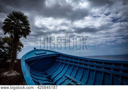 Blue Wooden Boat On The Bank Of Atlantic Ocean, Tenerife, Spain. Palm Tree, Cloudy Sky And Ocean In