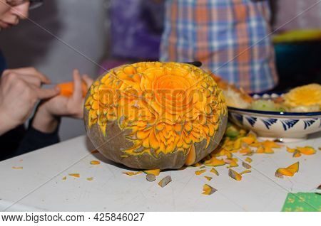 Carving A Pumpkin With A Beautiful Carved Flower On The Table, In The Background, Craftsmen Are Carv