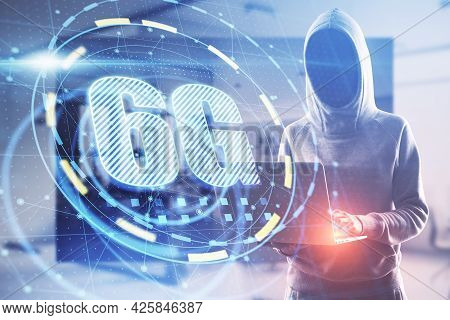 Hacker In Hoodie Using Computer With Glowing 6g Interface In Blurry Office Interior. Hacking, Theft