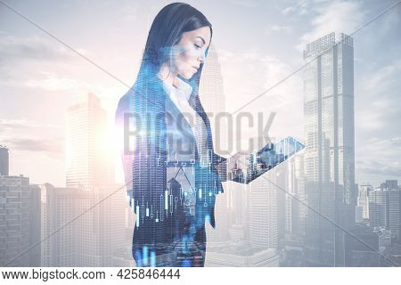 Attractive Young European Businesswoman Using Tablet Device On Abstract Bright City Background With