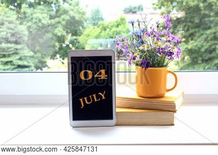 Calendar For July 4 : The Name Of The Month Of July In English And The Numbers 0 And 4 On The Tablet