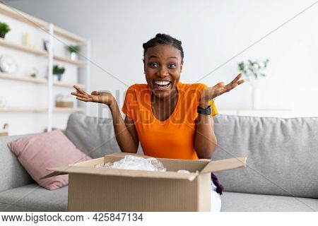 Excited Black Woman Receiving Parcel, Unpacking Cardboard Box At Home, Satisfied With Great Purchase