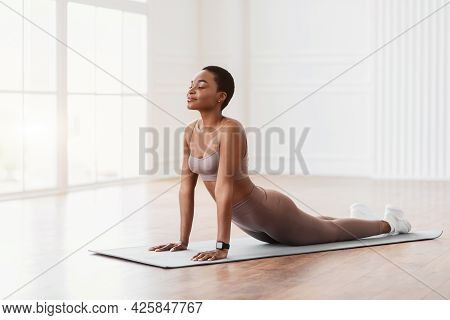 Young African Woman Stretching Back On Mat, Cobra Pose