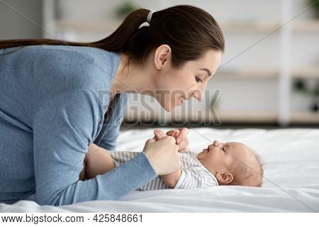 Mother-child Connection. Happy Loving Young Mommy Bonding With Newborn Child At Home