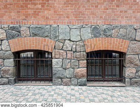 The Wall Is Made Of Large Granite Stones And Red Bricks. Two Windows With Bars In The Wall Of An Old