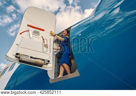 Smiling Stewardess Standing In The Doorway Of The Parked Plane