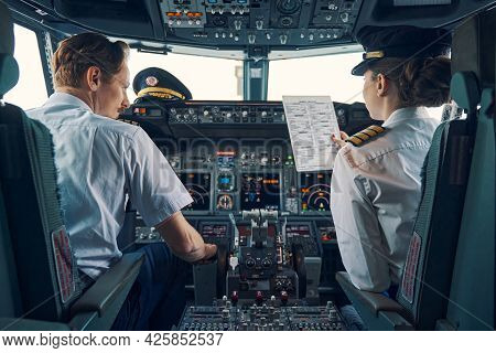 Pilot And Female First Officer Seated In The Flight Deck