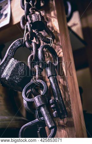 A Bunch Of Old Metal Keys Hanging On Dark Wooden Background, Close Up, Copy Space. Secret Symbol Or