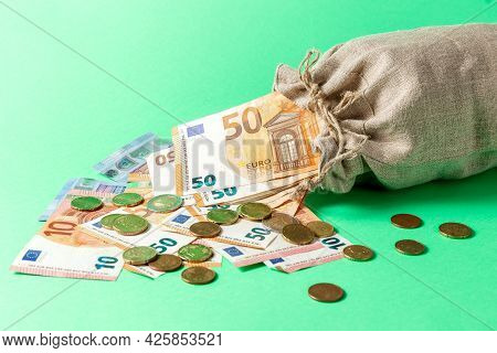 Money Bag On A Green Background. Euro Bills Are Scattered From The Bag. Wealth Concept.