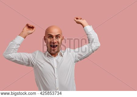 Good News. Ecstatic Overjoyed Bald Man With Bristle, Clenches Fists In Triumph, Happy With Sales, Dr