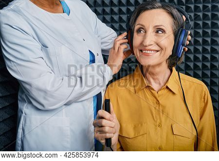 Portrait Senior Woman With White Toothy Smile While Hearing Check-up With Ent-doctor At Soundproof A