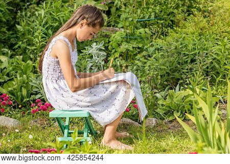 A Girl Sits On A Bench In The Garden With A Sketchbook On Her Lap And A Pencil In Her Hands. Her Fav