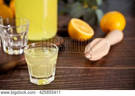 Italian Drink Lemon Liqueur Limoncello In A Bottle And Empty Glasses On The Wooden Table