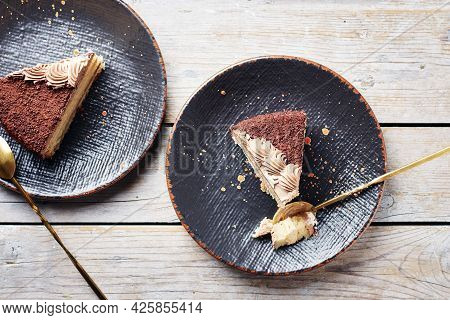 Two Pieces Of Chocolate Cake On Black Plates, Top View.
