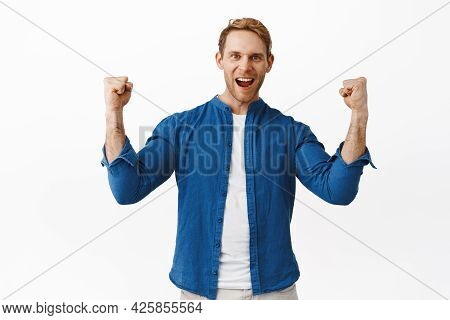 Encouraged And Determined Redhead Man Scream Yeah, Shaking Clenched Hands And Shouting Courageous, E