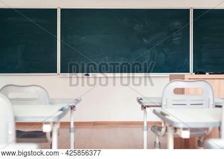 Empty School Classroom. Green Chalkboard On The Wall. Education Concept. Blackboard, Desks And Chair