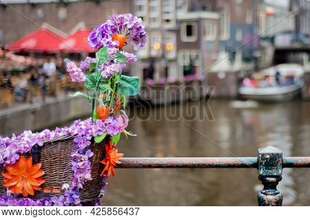 June 30, 2021, Amsterdam, Netherlands, Bicycle Decorated With Colorful Artificial Flowers Parked On