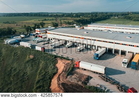 Trucks With Trailers Are Loaded And Unloaded In The Cargo Terminal In The Morning, Aerial Shot. Cont
