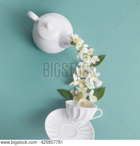 Layout Of Teapot And Tea Cup With Jasmine Flowers On A Green Background. Jasmine Tea.