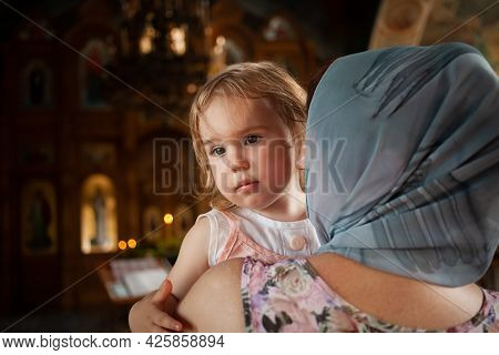 The Ritual Of Baptism. A Beautiful Christian Church Painted On The Walls Icons. Two-year-old Girl In
