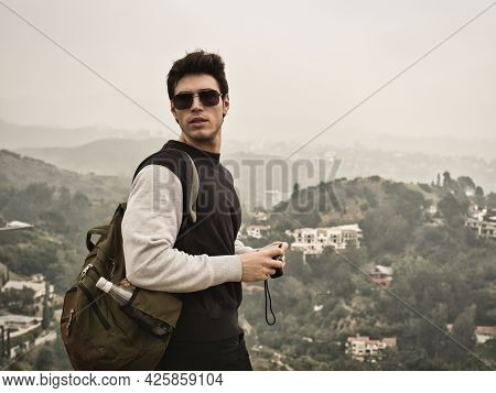 Male Photographer Or Tourist Standing Against Mountain Town