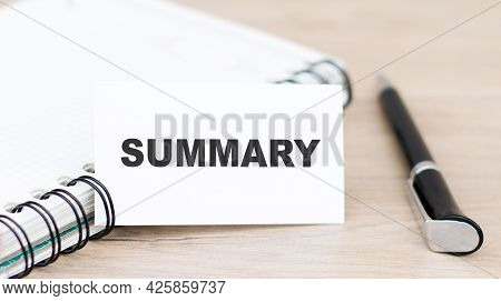 A White Card With The Word Summary On A Wooden Table Next To A Notepad And Black Pen.