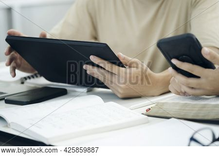 Close Up Young Hands Using Smartphones Synchronizing Information Online With Digital Tablet.