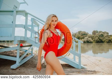 Young Attractive Blond Haired Woman In Red Swimsuit Like Lifeguard Posing With Lifeline On The Sand