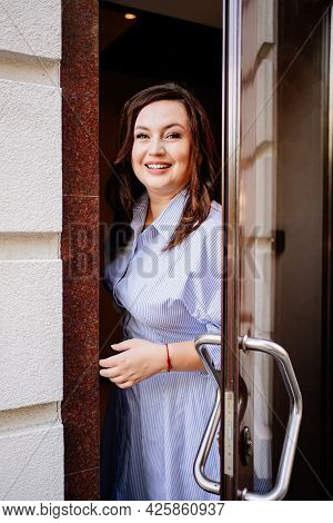 An Attractive Woman In A Blue Dress Stands In The Doorway.