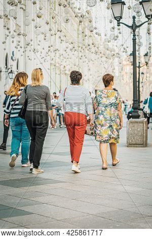 Back View Of Unrecognizable Young Women Walking On Street, Selective Focus. City Life. Regular Peopl