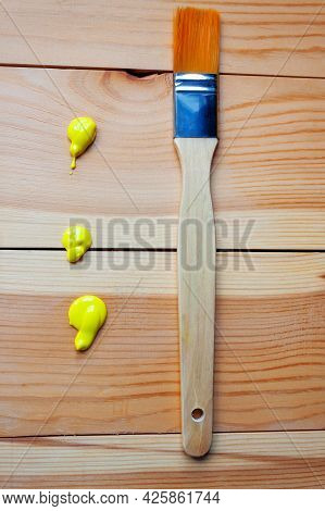 A Synthetic Bristle Brush Lies On Wooden Planks With Drops Of Yellow Acrylic Paint. Concept Of Art,