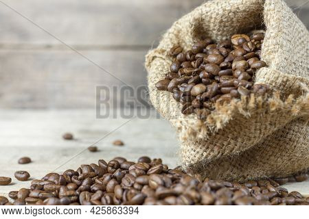 Roasted Coffee In A Burlap Sack On A Wooden Background. Coffee Beans Dropped Out On A Wooden Backgro