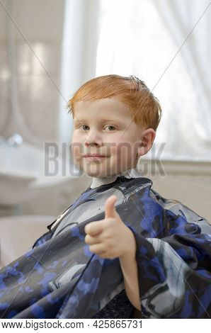 Red-haired Four-year-old Boy Smiling At The Barbershop. Joyful Child In The Barbershop