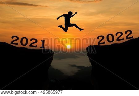 A Young Man Jump Between 2021 And 2022 Years Over The Sun And Through On The Gap Of Hill  Silhouette