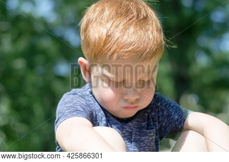The Child Is Offended. Portrait Of A 4-year-old Red-haired Boy Who Sits In The Sun And Takes Offense