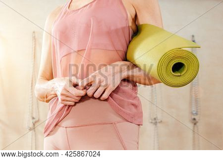 Woman Wearing Activewear Standing In Gym Holding Yoga Mat Ready To Start Fitness Or Yoga Training. C