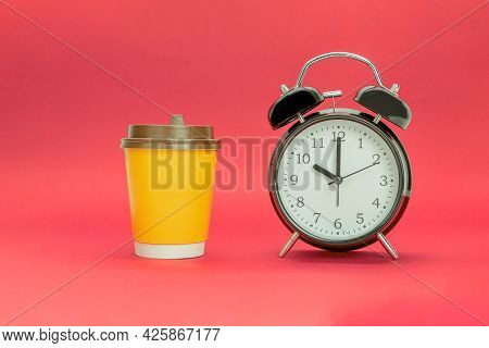 The Clock Indicates 10.00 And A Disposable Cup Of Coffee. Coffee Time Concept. Red Background With C