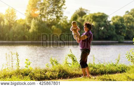 Grandmother Plays With Newborn Baby, Happy Elderly Woman Holds Her Grandchild In Hands. Granny And S