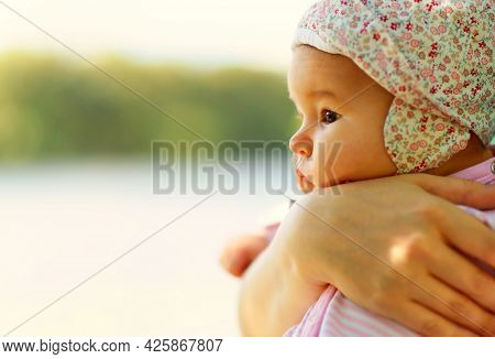Newborn Baby Outdoor, Mother Holds Her Small Child In Hands. Pensive Infant In Pink By River. Side V