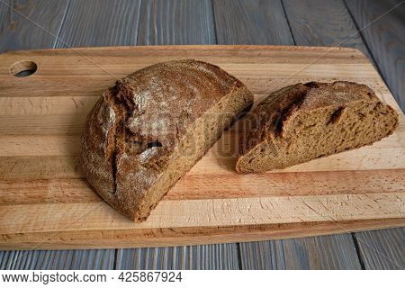 Bread. Sourdough Country Loaf. Freshly Baked With A Crunchy Crust On Top Of A Wooden Cutting Board.