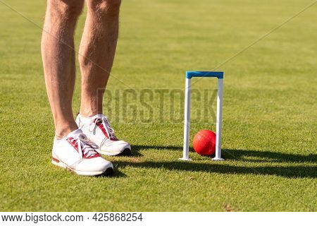 Male Croquet Player Hitting The Ball With Mallet