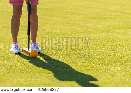 Female Croquet Player Hitting The Ball With Mallet
