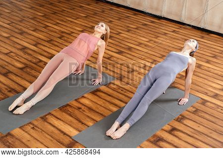 Two Women In Sportswear Practicing Yoga Asana Purvottanasana Doing The Reverse Plank
