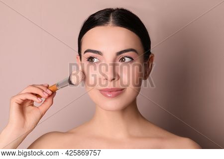 Beautiful Young Woman Applying Face Powder With Brush On Dusty Rose Background