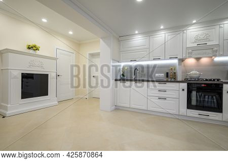 Modern large luxurious white kitchen interior with fireplace