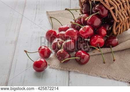 A Lot Of Sweet Cherry Berries Are Poured From A Wicker Basket On A Wooden Table, Summer Berry Backgr
