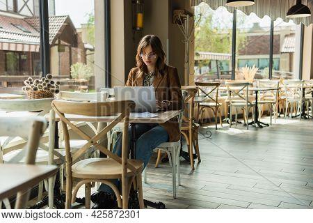 Stylish Teleworker Using Laptop Near Menu In Cafe.