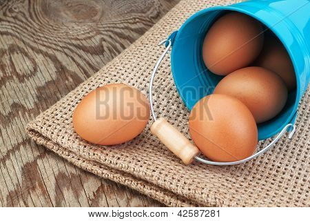 Blue bucket and easter eggs scattered on sackcloth. poster