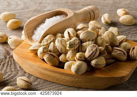 Heap Of Salted, Roasted Green Pistachio Nuts Snack In Wooden Bowl On Wood Background With Sea Salt I