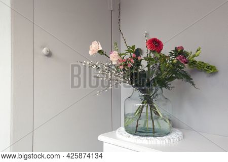 Beautiful Spring Flowers In Glass A Vase, Near Gray Wall In Stylish Home, Modern Interior Decoration